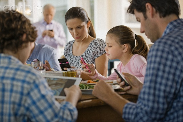 Family including kids (8-9) texting at dinner table